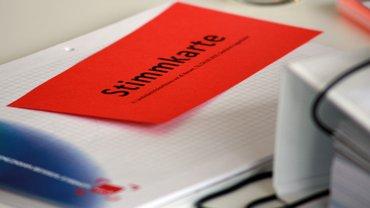 rote Stimmkarte liegt auf Block mit Orgawahllayout von 2015